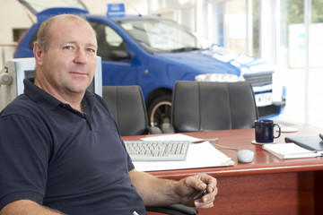 Car salesman sitting in showroom
