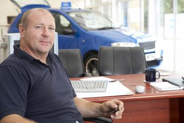 Car salesman sitting in showroom