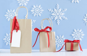 three brown paper packages on blue snowflake background for chri