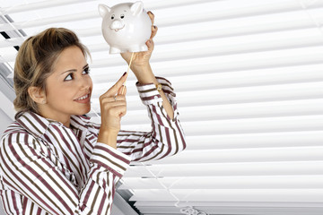 Young woman will putting money into piggy bank