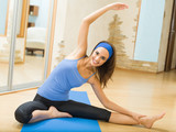 Fototapety Young happy woman exercising at home