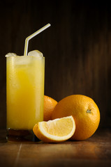 Oranges and orange juice in a glass on a dark background