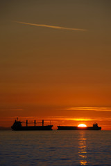 Cargo ships at sunset