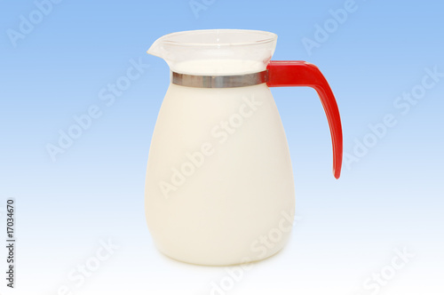 Glass jug of milk on blue background