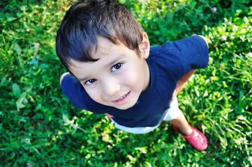A little cute boy standing on green ground