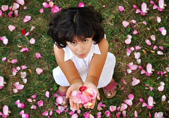 A little cute girl in white holding roses in hands