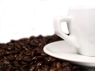 White cup of coffe on coffee beans background