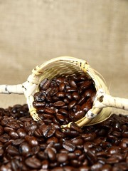 Wooden strainer with coffee beans on white background