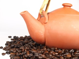 Ceramic chinese teapot with coffee beans on white background