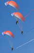 Three motor powered paragliders in blue sky