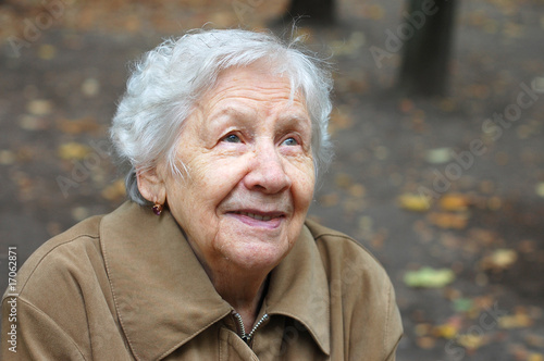 Portrait of the old woman on a autumn background