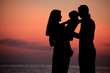 Silhouettes of parents with child on hands against  sea decline
