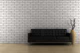 black sofa and vase with dry wood in front of brick wall