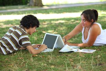 adolescents allongés dans l'herbe devant un ordinateur