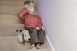 Upset little boy sitting on the stairs.