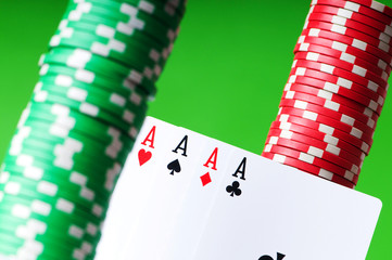 Casino chips and aces against green background