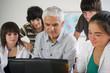 homme près d'adolescents devant un ordinateur portable