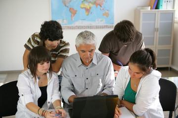 Adolescents devant un ordinateur portable près d'un homme