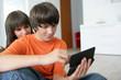 jeune garçon et fille assis avec une console portable