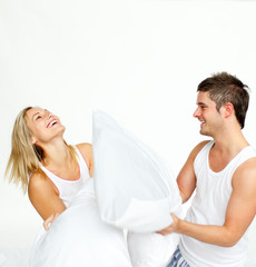 Young couple having a pillow fight with copy-space