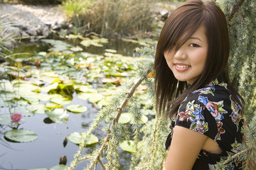 Brunette asian girl sitting at the lakeside.