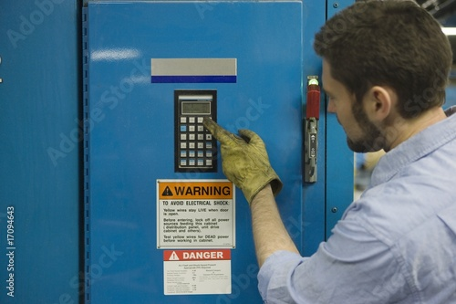 Man pressing keypad in newspaper factory
