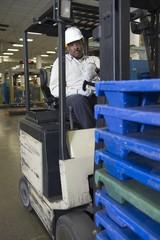 Man driving fork lift truck in newspaper factory