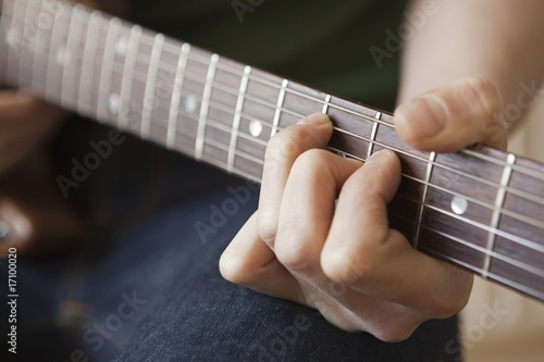 Young man playes chord on guitar
