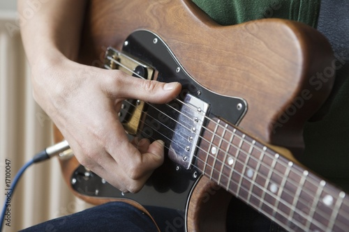 Young man strums chord on guitar