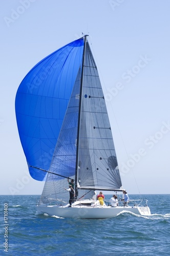 Yacht with blue sail competes in team sailing event, California