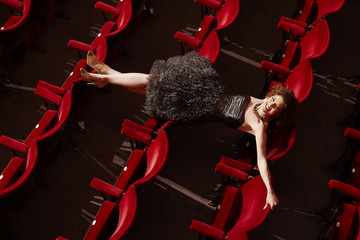 Woman lying on theatre stalls, high angle view