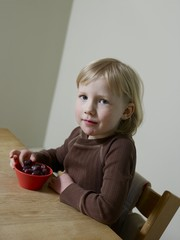 4-5 year old girl sits eating abowl of fruit