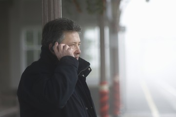 Man stands on train platform talking on mobile phone