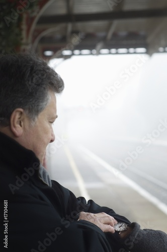 Man stands on train platform looking at watch