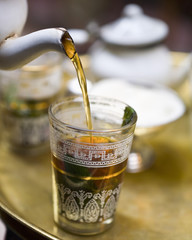 mint tea being poured into tea glass