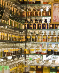 perfume bottles and pure scent on mirrored glass shelving unit