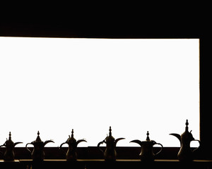 teapots backlit against brightly lit window