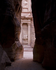 the ancient treasury at petra seen through the cracks of the rocks at the siq