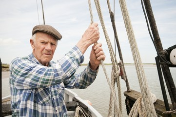Elderly man holds ropes of sailing boat