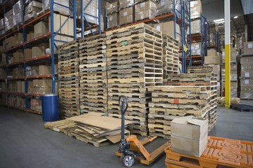 Wooden pallets stacked in distribution warehouse