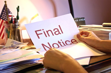 A person at their desk holding a paper that says Final Notice.
