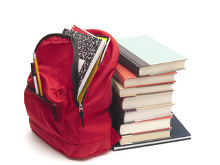 School backpack beside stack of books on white background