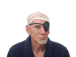 Senior man with bandaged head and eye patch
