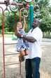 A father helps his daughter on the playground