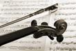 detail von violine und bogen vor notenblättern, sepia