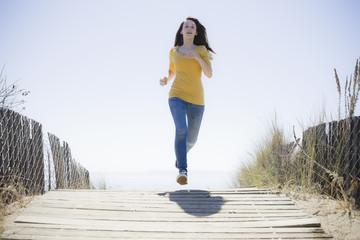 Girl Running On Beach Walkway