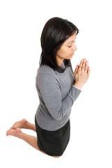 Business woman kneeling and praying