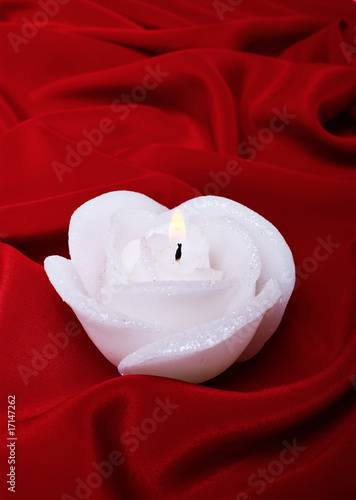 Candle in the form of a rose against silk