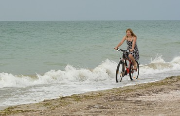 Girl goes by bike, to the appointment, near the sea.