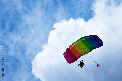 Skydiver flying in bright blue sky.